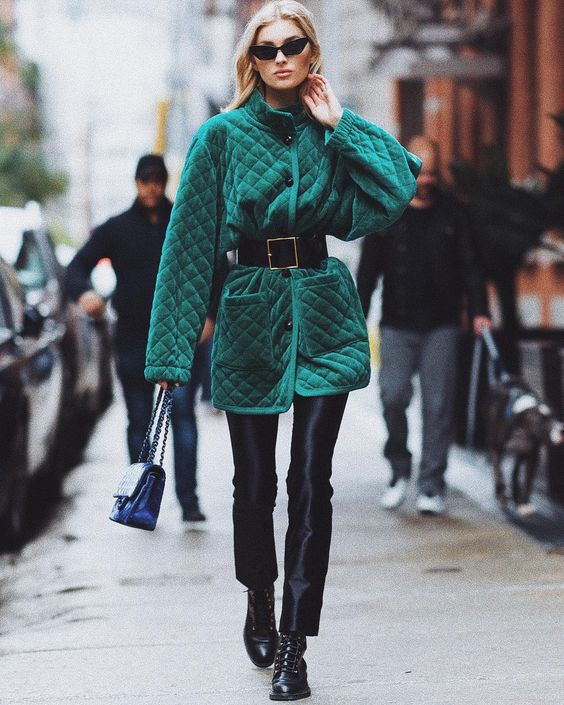 an emerald quilted coat with black buttons, a high neckline and a wide leather belt to accent the waist