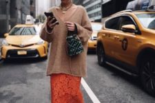 06 an oversized camel sweater with a deep V-neckline, a heavy chain, an orange lace maxi and printed shoes