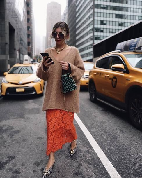 an oversized camel sweater with a deep V-neckline, a heavy chain, an orange lace maxi and printed shoes