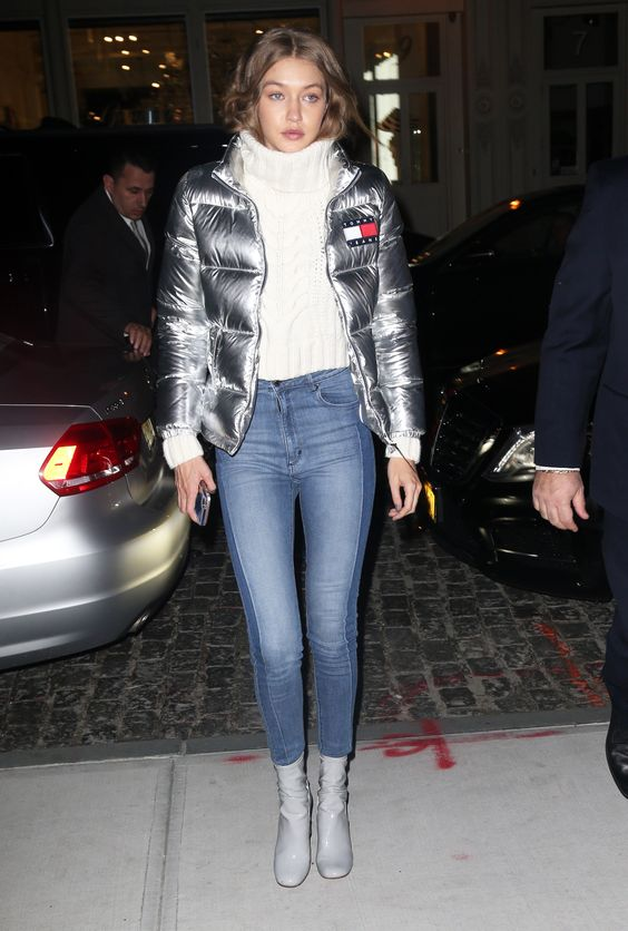 Gigi Hadid wearing blue cropped skinnies, grey boots, a white cropped sweater and a silver padded jacket