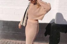07 a blush knit suit with a crop top with long sleeves and a pencil midi skirt, white trainers and a snake bag
