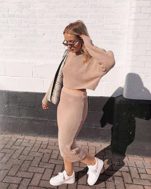 a blush knit suit with a crop top with long sleeves and a pencil midi skirt, white trainers and a snake bag