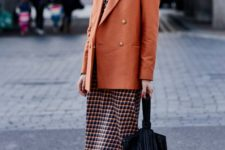 07 a stylish printed midi dress, a rust-colored oversized blazer, white boots and a black bag for a retro-inspired look