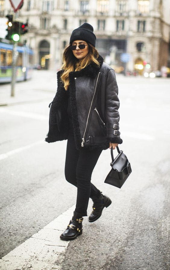 a total black look with a top, skinnies, belted and buckle boots, an aviator jacket and a beanie