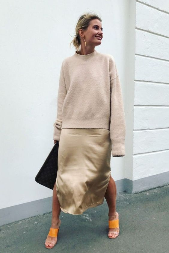 a neutral silk slip midi dress, a matching neutral sweatshirt and bold orange shoes and a black bag