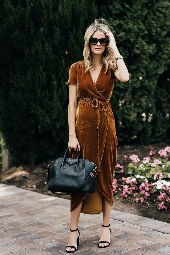 a rust-colored velvet wrap midi dress, black heels and a black bag for a fall-colored Thanksgiving look