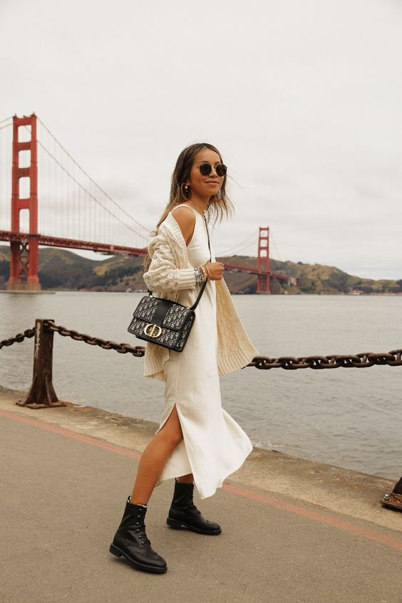a white slip midi dress, a creamy oversized knit cardigan, black combat boots and a black bag