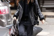 09 Keira Knightlery wearing a black top, black mom jeans, brown boots and a black aviator coat