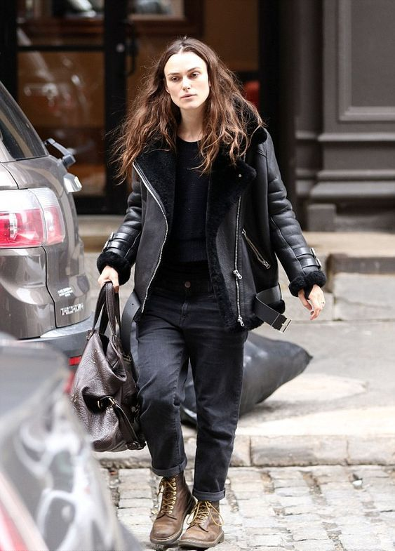 Keira Knightlery wearing a black top, black mom jeans, brown boots and a black aviator coat