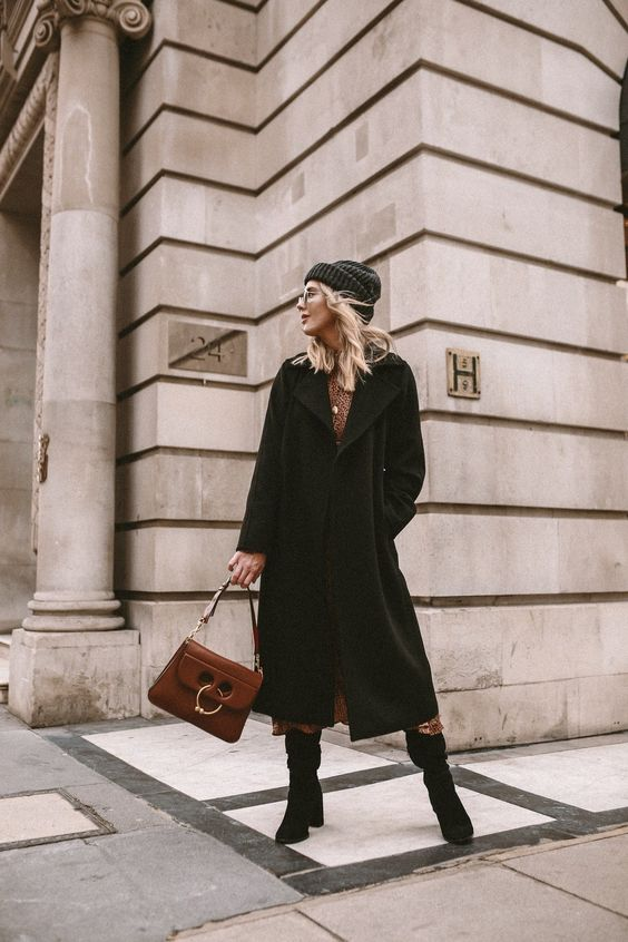 a cozy winter outfit with a brown printed midi dress, a black wrap midi coat, blakc boots and a beanie