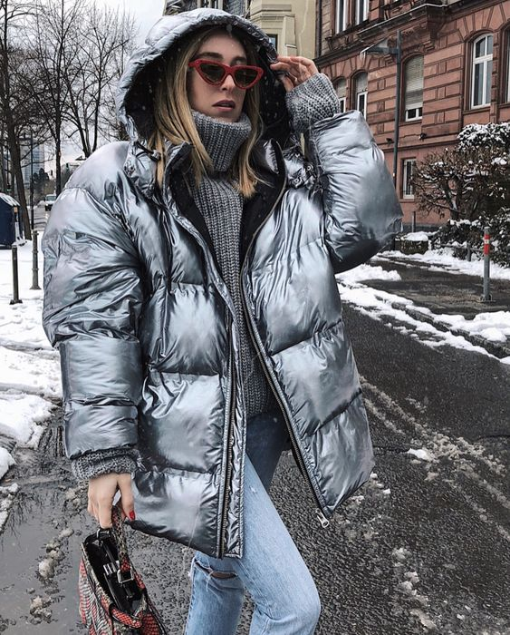 a trendy look with an oversized grey sweater, blue jeans, a silver puffer jacket and a snake bag