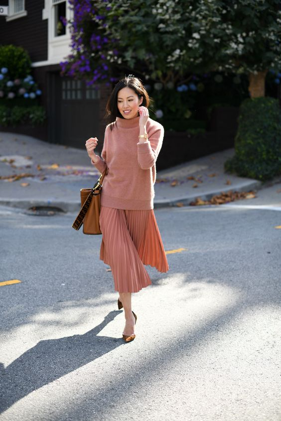 an oversized coral sweater, a matching pleated midi and brown velvet shoes plus an amber bag