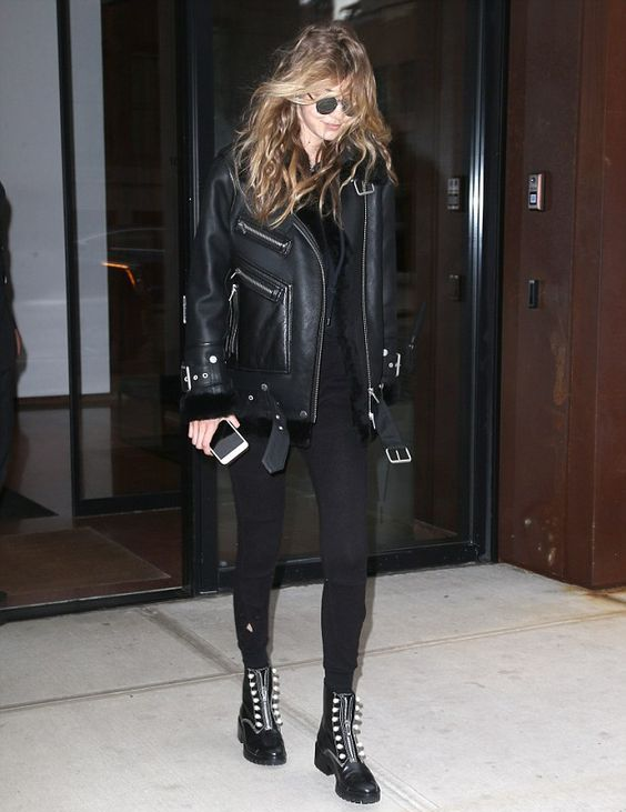 Gigi Hadid wearing a black top and leggings, black boots and a black aviator coat
