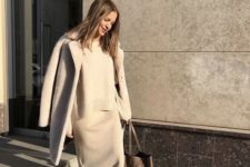 10 a minimalist look with a grey knit suit with a midi skirt, white sneakers and a grey coat plus a brown tote