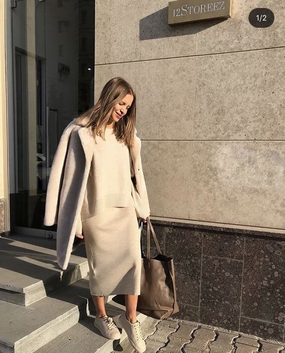 a minimalist look with a grey knit suit with a midi skirt, white sneakers and a grey coat plus a brown tote