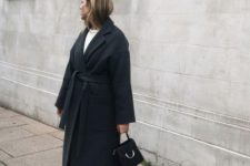 10 a simple and minimalist winter outfit with a white top, blakc pants, black heeled booties, a black wrpa coat and a black bag