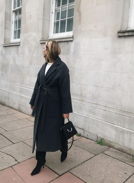 a simple and minimalist winter outfit with a white top, blakc pants, black heeled booties, a black wrpa coat and a black bag