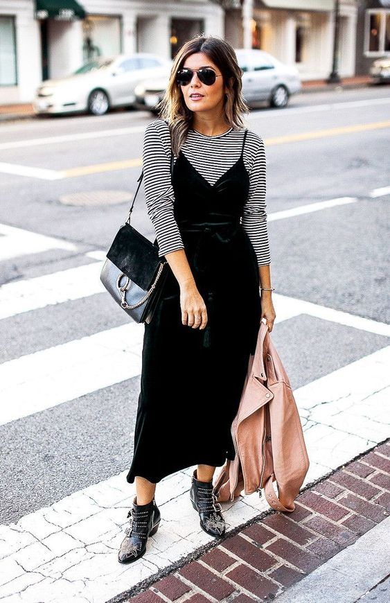 a striped long sleeve top, a black velvet slip dress, a black bag and black studded boots plsu a blush leather jacket