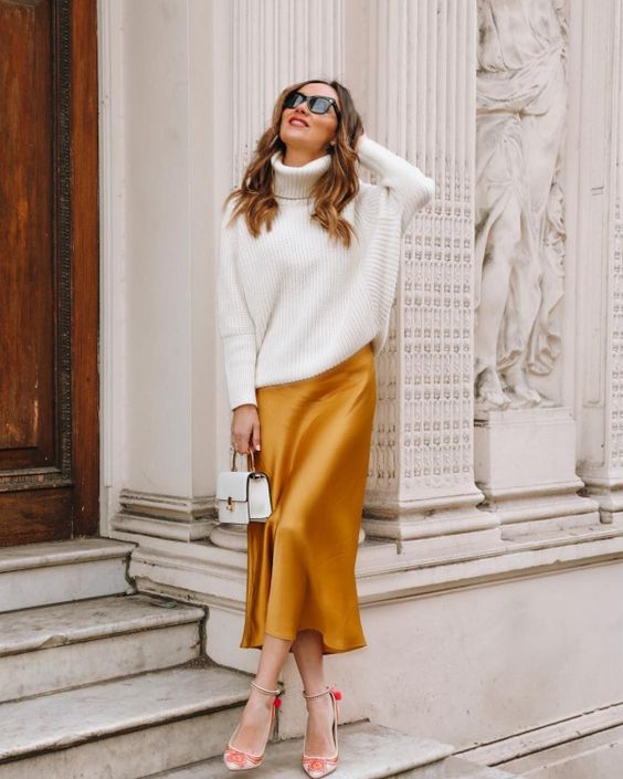 an oversized white turtleneck sweater, a marigold silk midi skirt, floral shoes and a tiny white bag