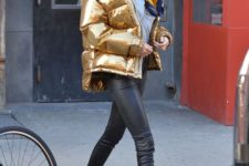 11 Kendall Jenner wearing black leather pants, a grey tee, black lacquer boots and a gold puffer jacket