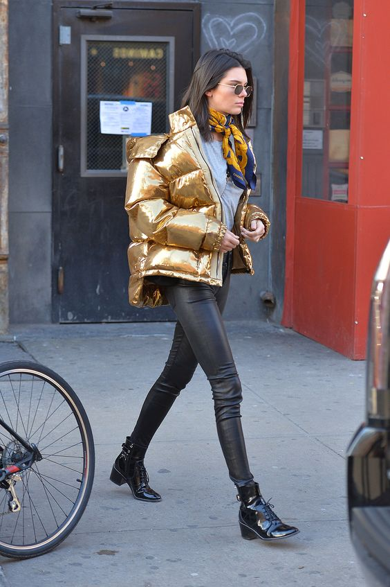Kendall Jenner wearing black leather pants, a grey tee, black lacquer boots and a gold puffer jacket