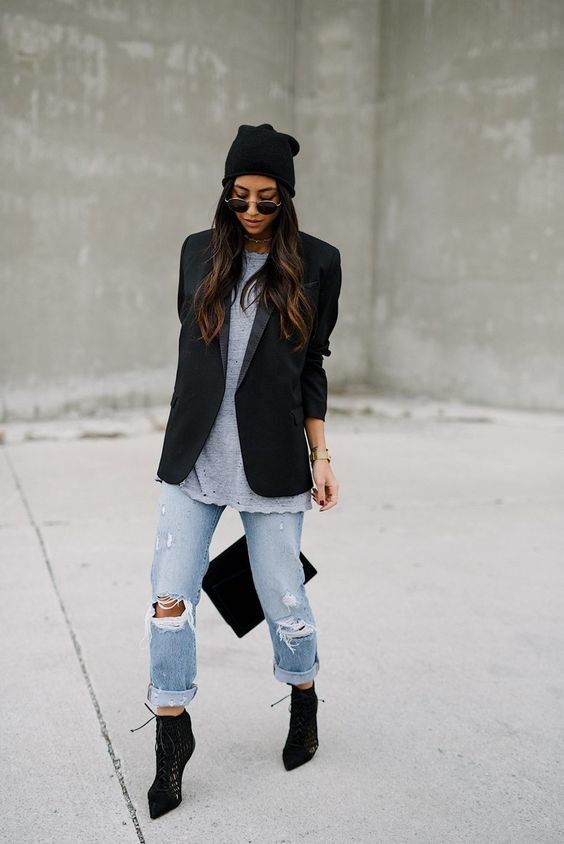 a black oversized blazer, a long dotted tee, blue ripped jeans, black sock boots and a beanie