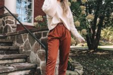 11 a casual look with rust-colored high-waisted pants, grey boots, a white top with knit sleeves