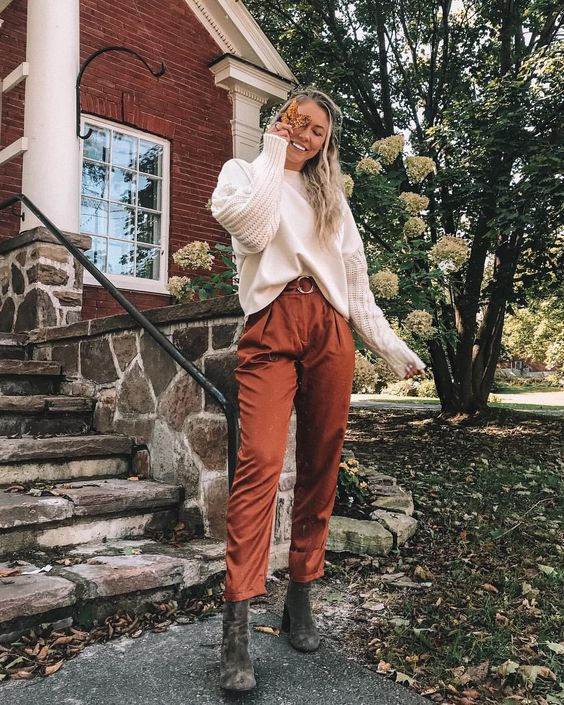 a casual look with rust-colored high-waisted pants, grey boots, a white top with knit sleeves