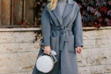 11 a monochromatic outfit with a turleneck sweater dress, a grey wrap coat with pockets, grey tall boots and a bag
