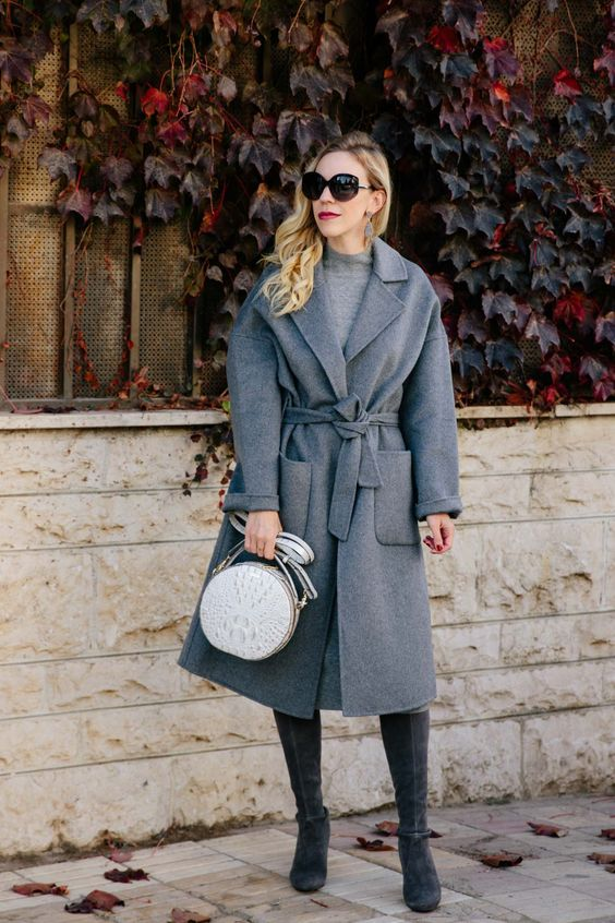 a monochromatic outfit with a turleneck sweater dress, a grey wrap coat with pockets, grey tall boots and a bag