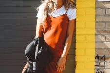 11 a white tee, an orange silk slip dress, whiet sneakers and a black lrather jacket for a timeless fall look