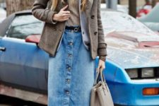 11 a winter outfit with a neutral top, a blazer and a coat, a blue denim midi, burgundy tights, grey trainers and a beanie