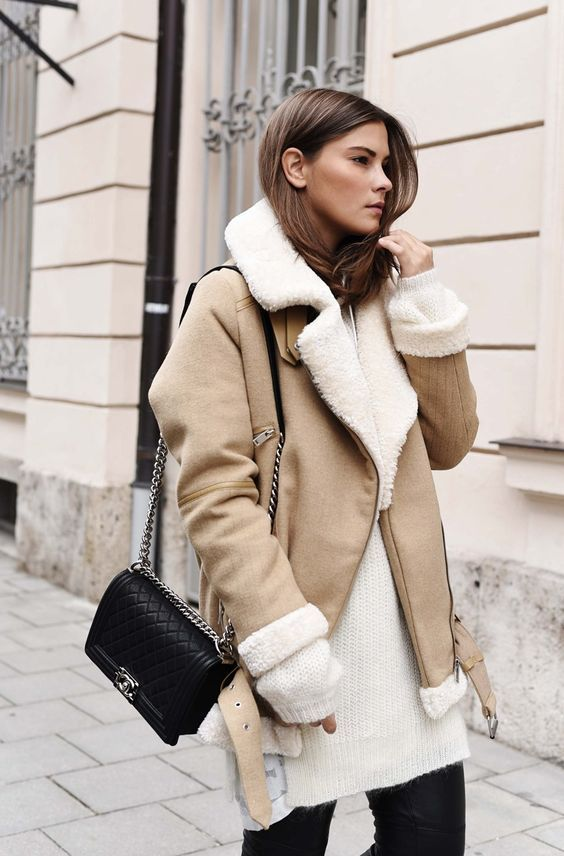 an oversized white sweater, black leather pants, a neutral and white aviator coat and a black bag