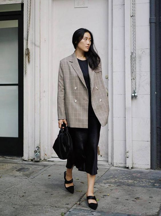 a black slip midi dress, an oversized plaid blazer, black shoes and a black bag for an edgy touch