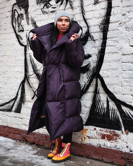 a trendy and bold look with colorful boots, a black blanket padded coat, a grey beanie