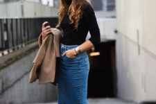 12 an elegant and simple look of a black turtleneck, a blue denim midi skirt with a front slit, black heels and a camel jacket