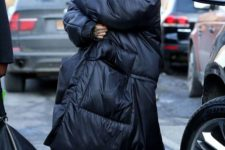13 Rihanna wearing a black blanket padded coat and super refined black and white lace up booties