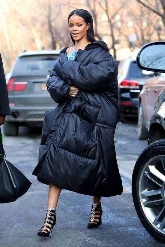 Rihanna wearing a black blanket padded coat and super refined black and white lace up booties