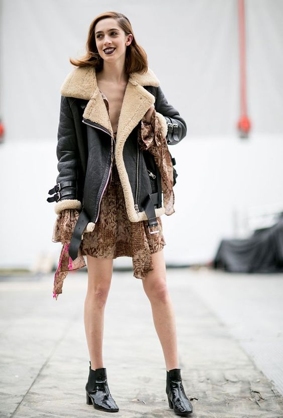a brown printed mini dress, black lacquer booties and a black and neutral aviator coat