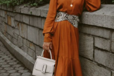 13 a chic look with a rust-colored midi dress, a wide snake print belt and black booties for the fall