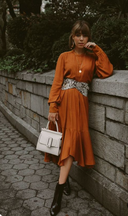 a chic look with a rust-colored midi dress, a wide snake print belt and black booties for the fall