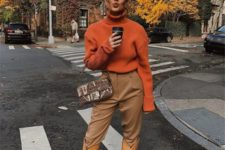13 a fashionista look with a rust-colored sweater, tan pants, yellow cowboy boots and a printed bag