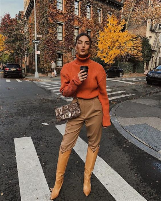 a fashionista look with a rust-colored sweater, tan pants, yellow cowboy boots and a printed bag