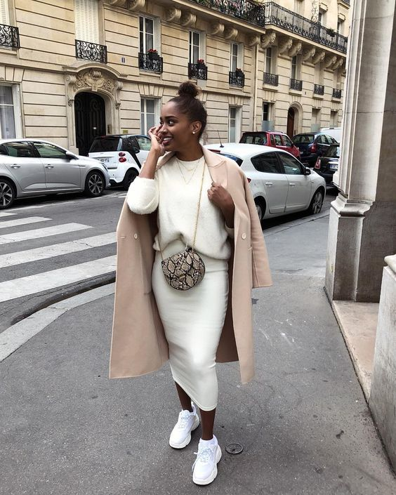 a pure white knit suit with a midi pencil skirt, white trainers, a creamy coat and a snake print bag