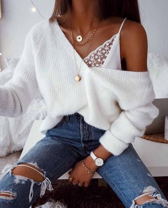 a sexy look with an oversized white pullover, blue ripped jeans, a lace bralette and layered necklaces
