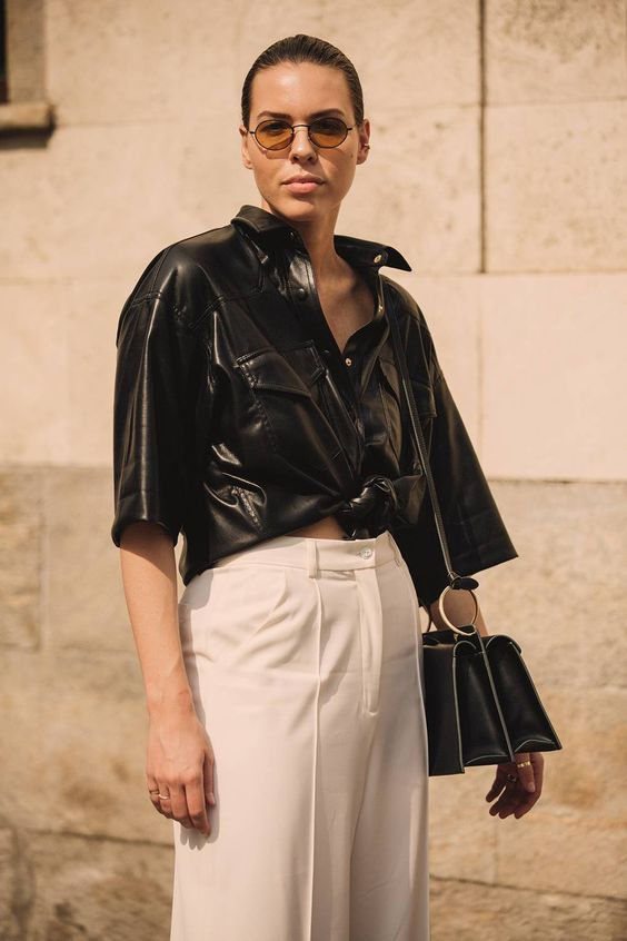 a trendy minimalist look with a black leather shirt, white wideleg pants, a black bag