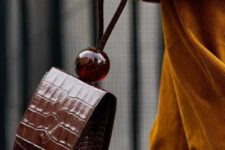 13 a very statement brown crocodile leather bag with a handle decorated with an oversized ball