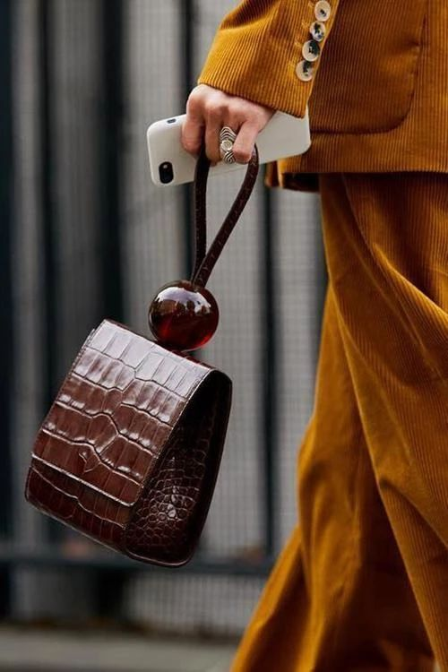 a very statement brown crocodile leather bag with a handle decorated with an oversized ball