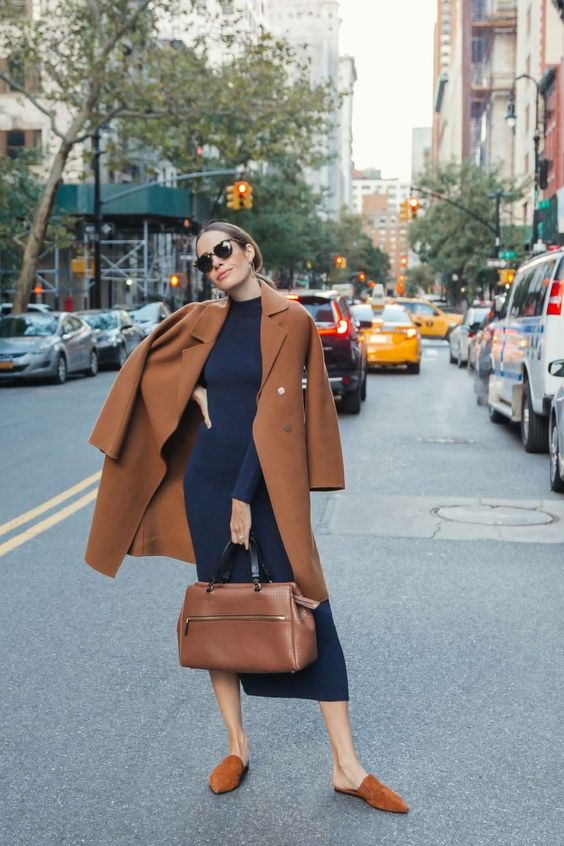 a work look with a navy sweater dress, a camel straight coat, a matching bag and camel slip loafers