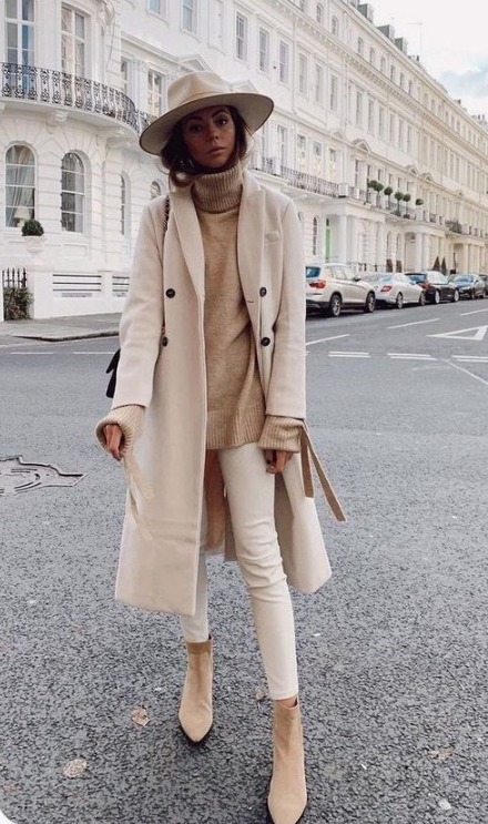 a neutral monochromatic outfit with a neutral fedora hat paired with a coat looks very pretty and very chic